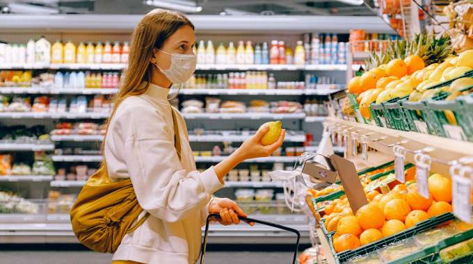 Woman budget-shopping for groceries with mask on
